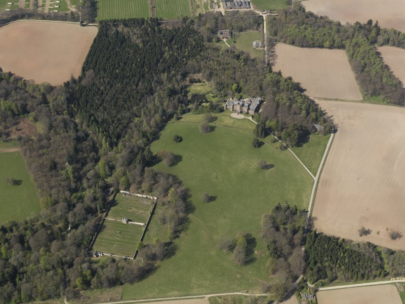 Oblique aerial view of the country house with the walled garden adjacent, taken from the SE.