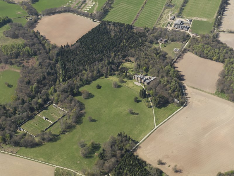 Oblique aerial view of the country house with the walled garden adjacent, taken from the ESE.