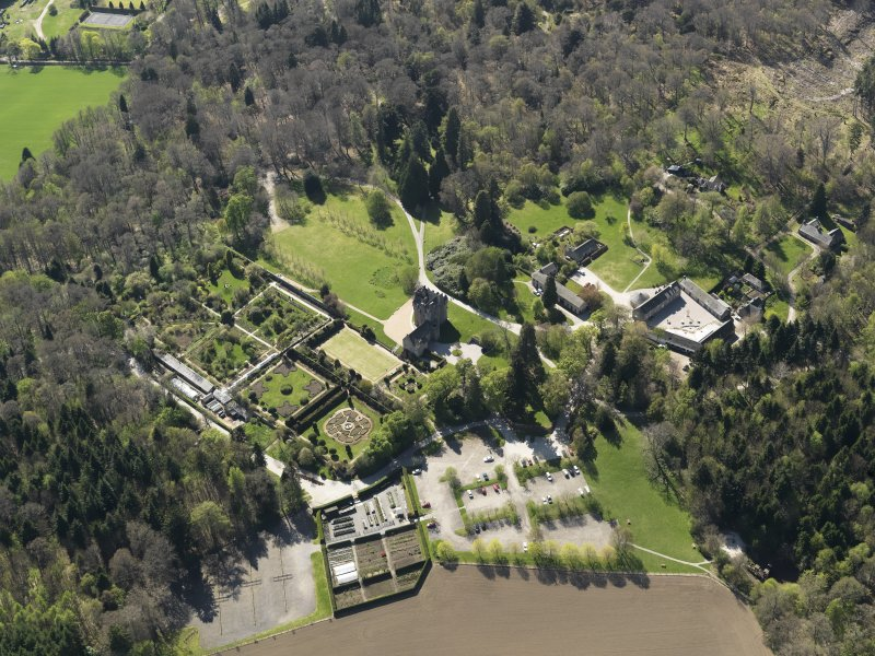 Oblique aerial view centred on the castle with the garden adjacent, taken from the NE.