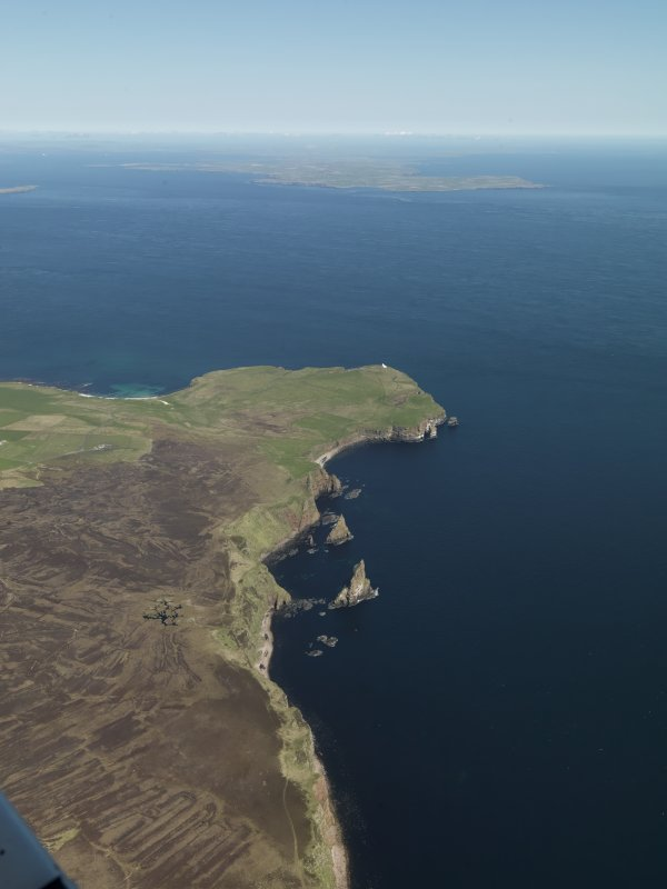 General oblique aerial view looking towards Duncansby Head lighthouse with South Ronaldsay beyond, taken from the SSW.