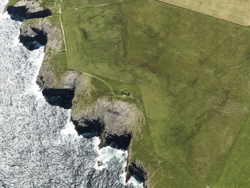 Oblique aerial view centered on the remains of the Tomb of the Eagles chambered cairn, Isbister on South Ronaldsay, taken from the NE.