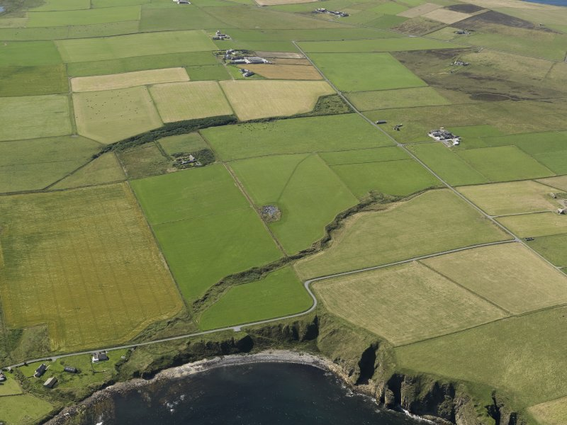 Oblique aerial view centred on the excavation of the Cairns o' the Bu settlement at Windwick, taken from the ENE.