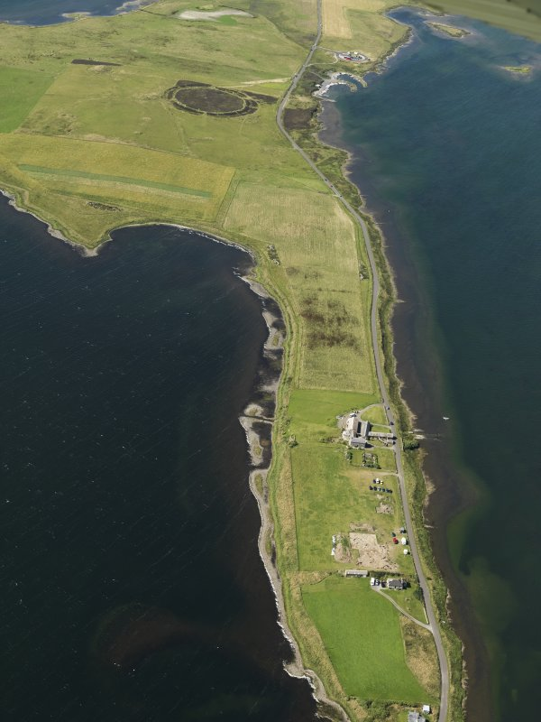 General oblique aerial view centred on the excavations of Brodgar settlement with the Ring of Brodgar beyond, taken from the SSW.