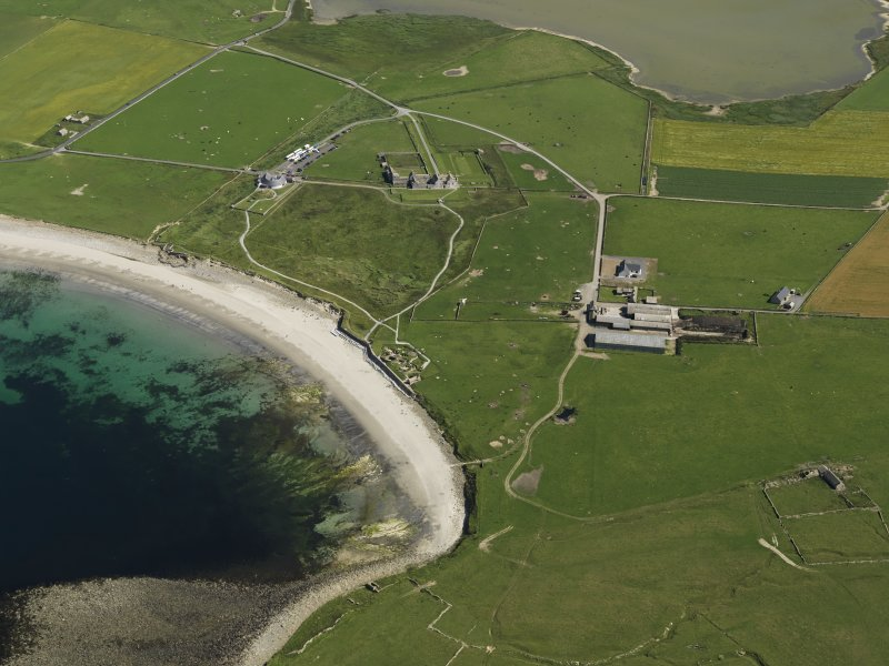Oblque aerial view centred on the neolithic settlement at Skara Brae, Bay of Skaill, with Skaill House adjacent, taken from the W.
