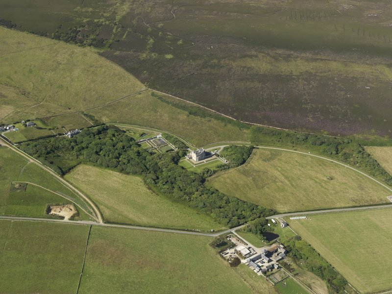 Oblique aerial view centered on the chambered cairn at Taversoe Tuck with Trumland House adjacent, taken from the SSE.
