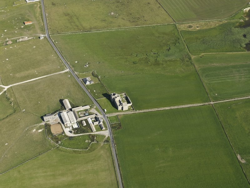 Oblique aerial view centred on the ruins of Noltland Castle with Noltland farmsteading adjacent, taken fromt he WNW.