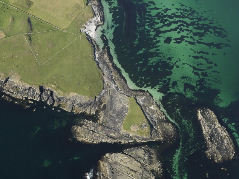 Oblique aerial view centred on the Knowe of Skea broch and the excavation of the cemetery, taken from the SSW.