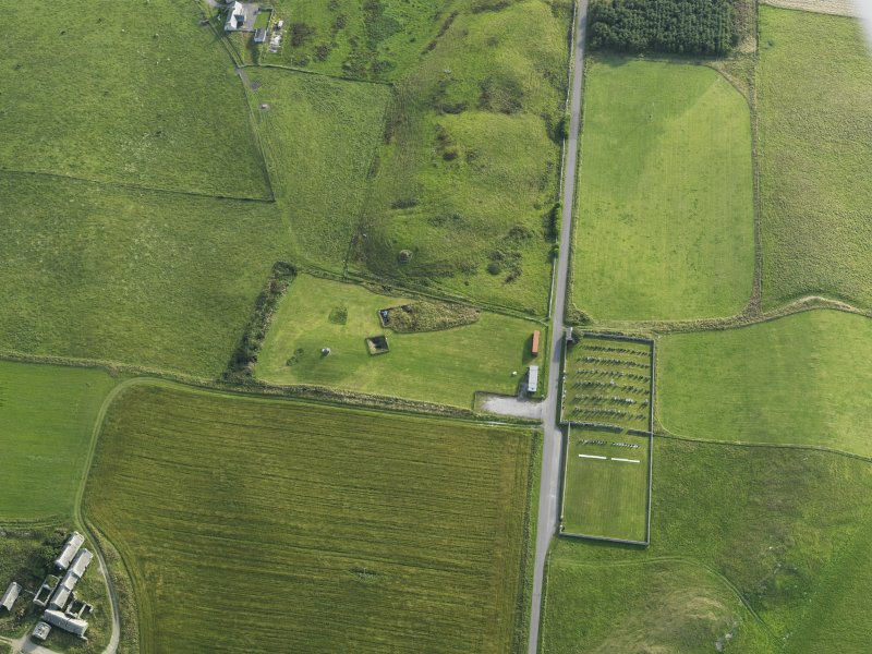 Oblique aerial view centred on Mine Howe with St Ninian's Chapel adjacent, taken from the SW.