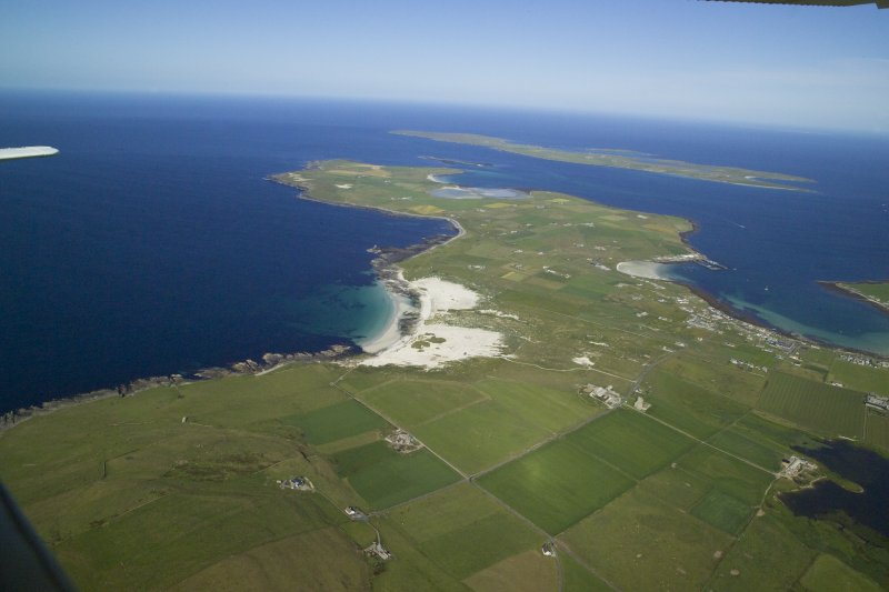 General oblique aerial view of the N of Westray centred on Links of Noltland settlement, taken from the W.