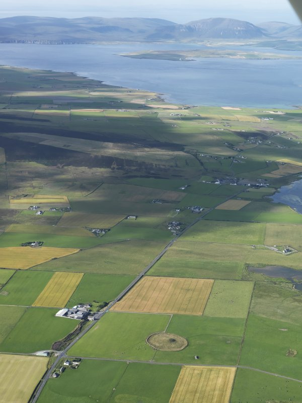 General oblique aerial view of the Loch of Stenness with Maes Howe in the foreground and Hoy in the distance, taken from the NE.