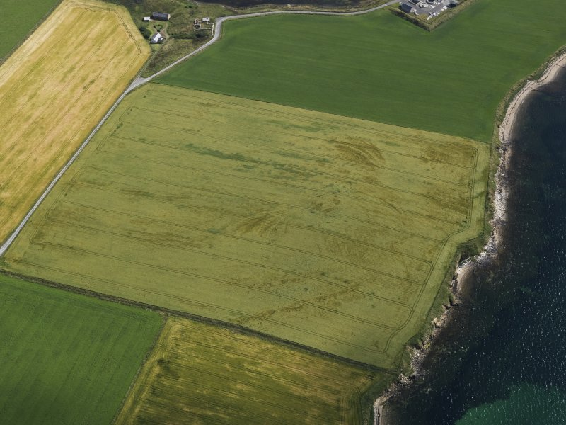 Oblique aerial view centred on the cropmarks of the broch at Bu, taken from the SW.