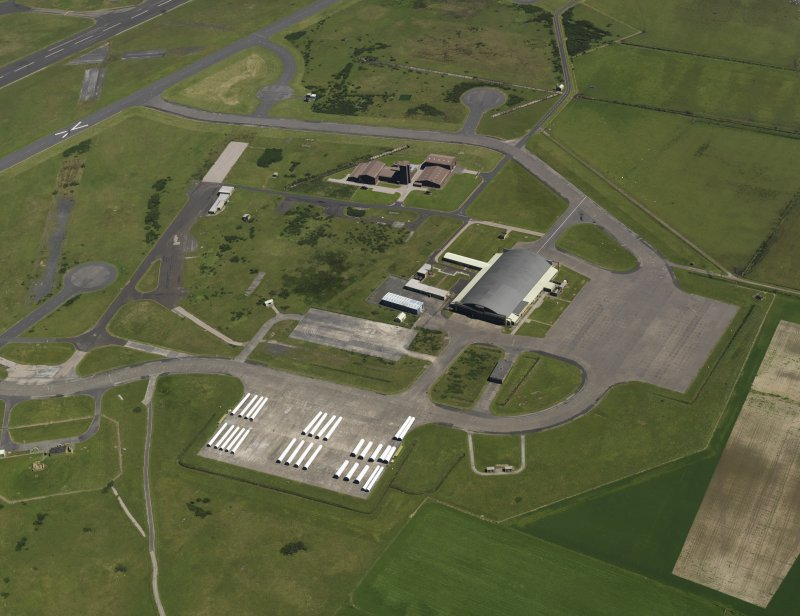 General oblique aerial view centred on the 'Gaydon' aircraft hangar with the USN base adjacent, taken from the WSW.