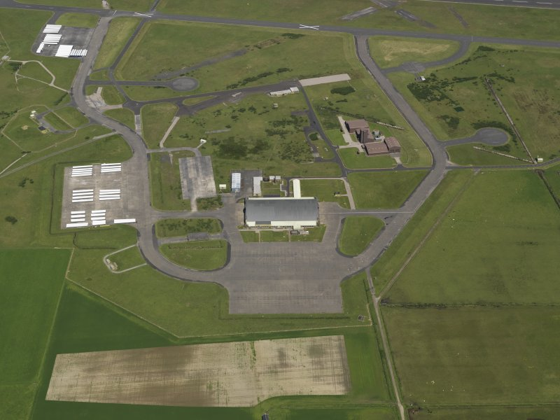 General oblique aerial view centred on the 'Gaydon' aircraft hangar with the USN base adjacent, taken from the S.