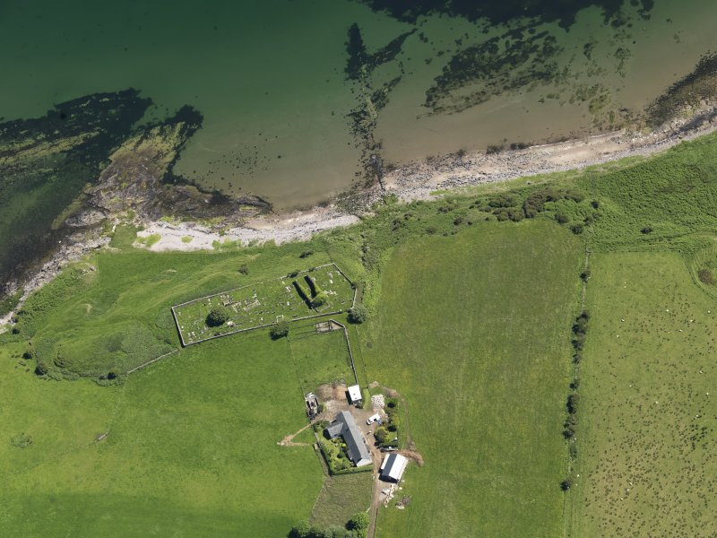 Oblique aerial view centred on the remains of the church with the farmstead adjacent, taken from the W.