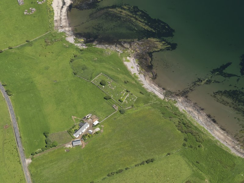 Oblique aerial view centred on the remains of the church with the farmstead adjacent, taken from the SW.
