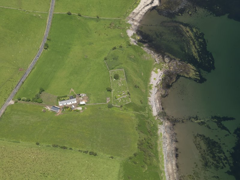 Oblique aerial view centred on the remains of the church with the farmstead adjacent, taken from the S.