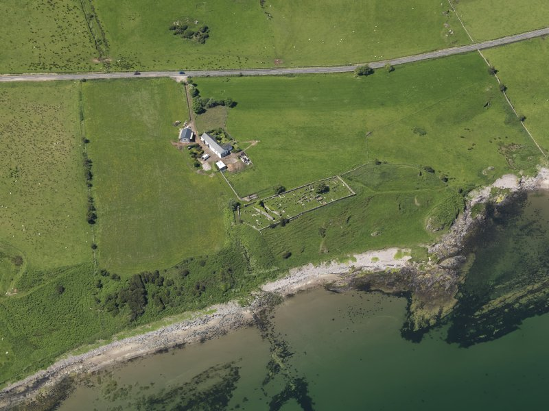Oblique aerial view centred on the remains of the church with the farmstead adjacent, taken from the E.