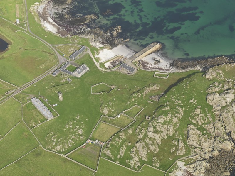 Oblique aerial view centred on Hynish farm steading with Hynish farmhouse adjacent, taken from the SSW.