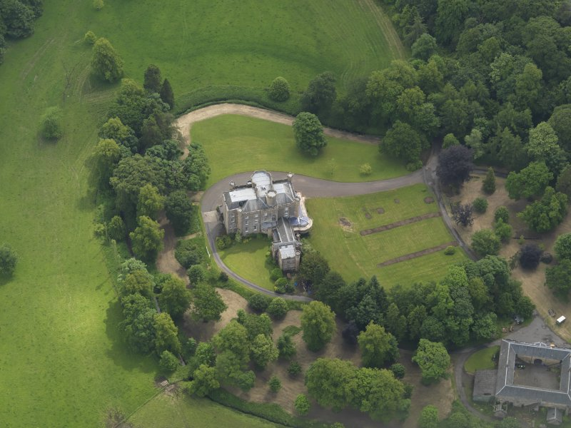 Oblique aerial view of Caprington Castle and stables, taken from the WNW.