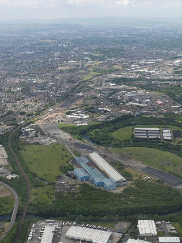 General oblique aerial view centred on the steel works with the motorway extension works adjacent, taken from the E.