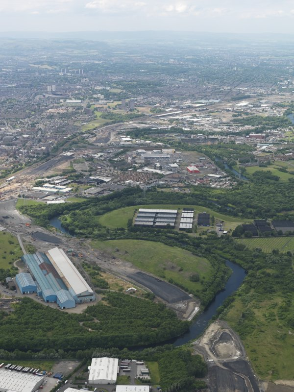 General oblique aerial view centred on the steel works with the motorway extension works adjacent, taken from the ENE.