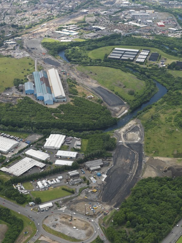 General oblique aerial view centred on the steel works with the motorway extension works adjacent, taken from the NE.