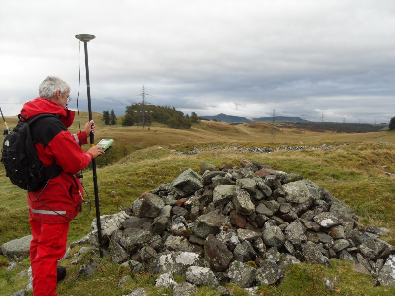 General view of Mr Ian Parker (RCAHMS) using differential GPS to survey a small cairn overlying the inner wall of the timber-laced fort.