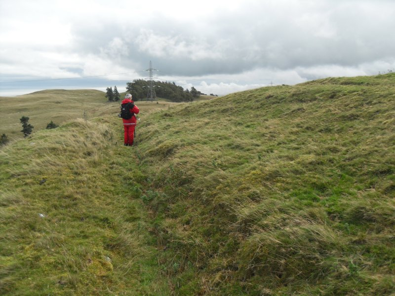 Mr Ian Parker (RCAHMS) using differential GPS to survey a late 19th century excavation trench cutting through a circular house platform on the N side of the timber-laced fort.
