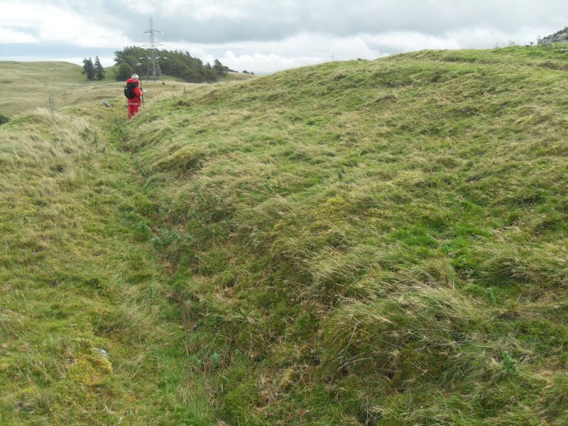 View from W of Mr Ian Parker (RCAHMS) using differential GPS to survey a late 19th century excavation trench cutting through a circular house platform on the N side of the timber-laced fort.