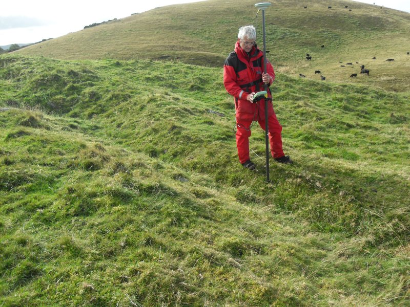 View of Mr Ian Parker (RCAHMS) using differential GPS to survey a late 19th century excavation trench at the W end of the timber-laced fort.