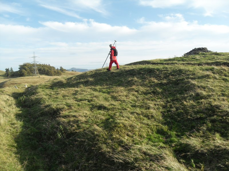 View from W of Mr Ian Parker (RCAHMS) using differential GPS to survey a circular house platform on the N side of the timber-laced fort.