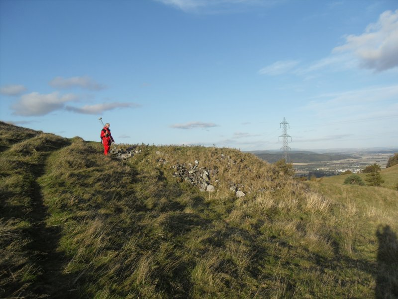 View from S of Mr Ian Parker (RCAHMS) using differential GPS to survey a late 19th century stone dump outside the E end of the timber-laced fort, the result of excavation by Edwin Weston Bell.