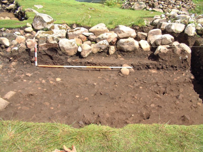 Trench 14 from the W showing excavation of main burnt mound deposits C14.13 and back (E) wall of shieling 2 (scale = 0.2m)