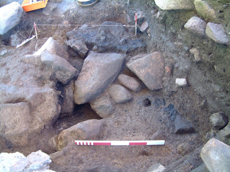 Trench 15, after part excavation of pit feature F15.10 from the E, showing charcoal rich C14.20 and stone (scale = 0.5m)
