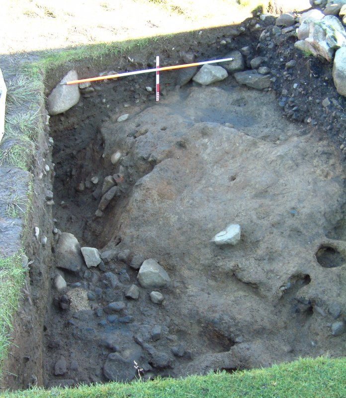 Trench 14 from the S showing S-facing baulk, natural karstic clay, revetment wall F14.12, hearth setting F14.14 and deposits falling away into pit feature (scales = 2m and 0.5m)