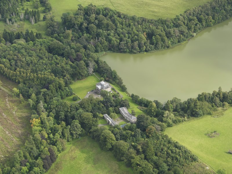 Oblique aerial view centred on the country house with the stable block adjacent, taken from the WNW.