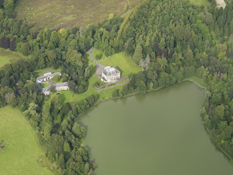 Oblique aerial view centred on the country house with the stable block adjacent, taken from the SSW.