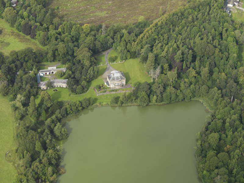 Oblique aerial view centred on the country house with the stable block adjacent, taken from the S.
