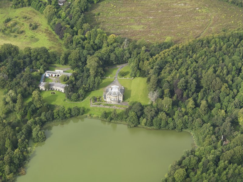 Oblique aerial view centred on the country house with the stable block adjacent, taken from the SSE.