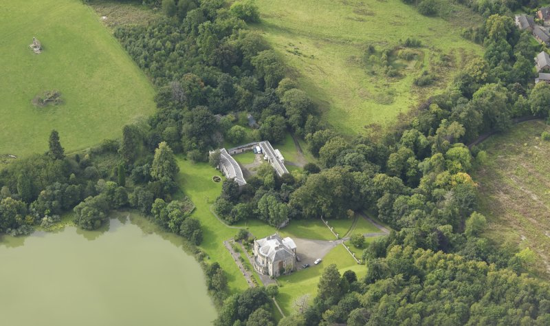 Oblique aerial view centred on the country house with the stable block adjacent, taken from the ESE.