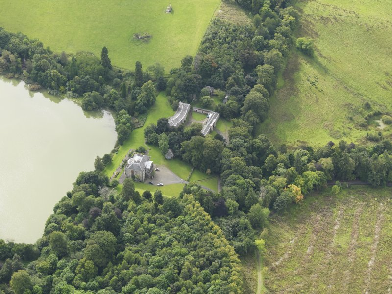 Oblique aerial view centred on the country house with the stable block adjacent, taken from the ENE.