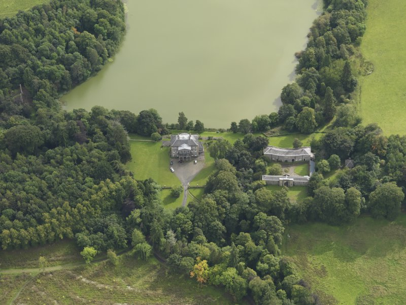 Oblique aerial view centred on the country house with the stable block adjacent, taken from the N.
