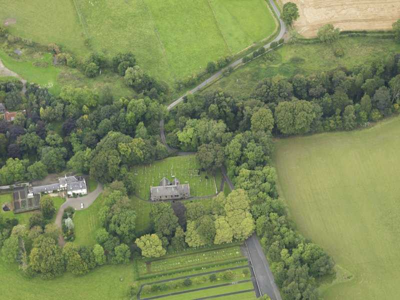Oblique aerial view centred on the church with the churchyard and manse adjacent, taken from the SSE.