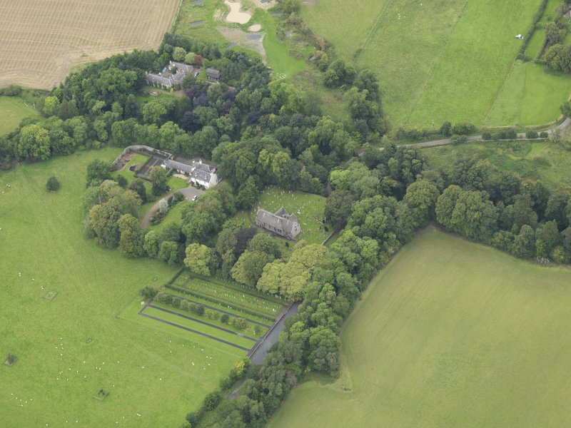 Oblique aerial view centred on the church with the churchyard and manse adjacent, taken from the ESE.