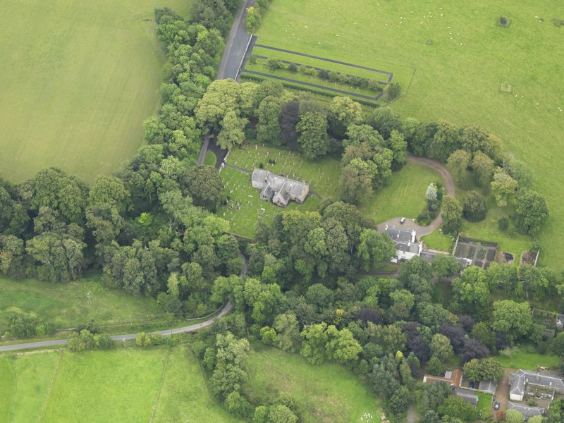 Oblique aerial view centred on the church with the churchyard and manse adjacent, taken from the NNW.