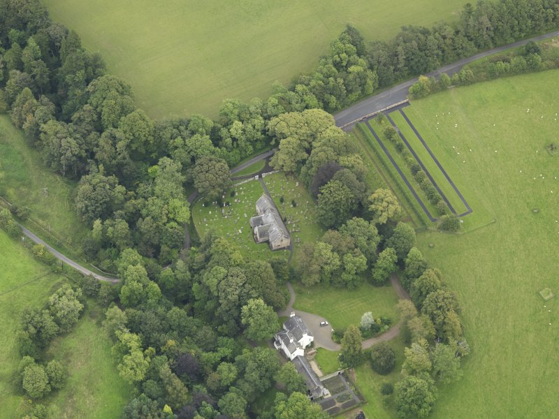 Oblique aerial view centred on the church with the churchyard and manse adjacent, taken from the W.