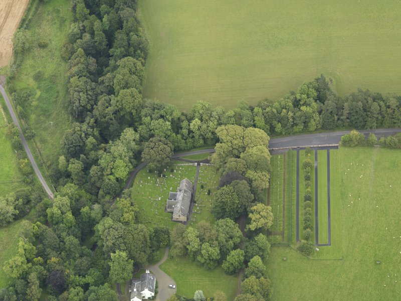Oblique aerial view centred on the church with the churchyard and manse adjacent, taken from the WSW.