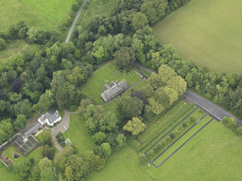 Oblique aerial view centred on the church with the churchyard and manse adjacent, taken from the SW.