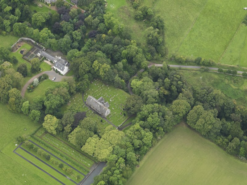 Oblique aerial view centred on the church with the churchyard and manse adjacent, taken from the SE.