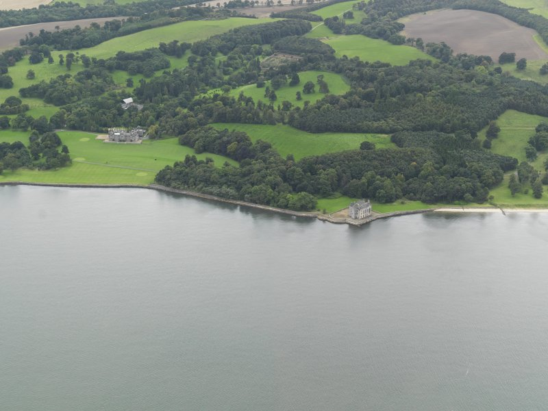 General oblique aerial view centred on the country house with Barnbougle Castle adjacent, taken from the N.